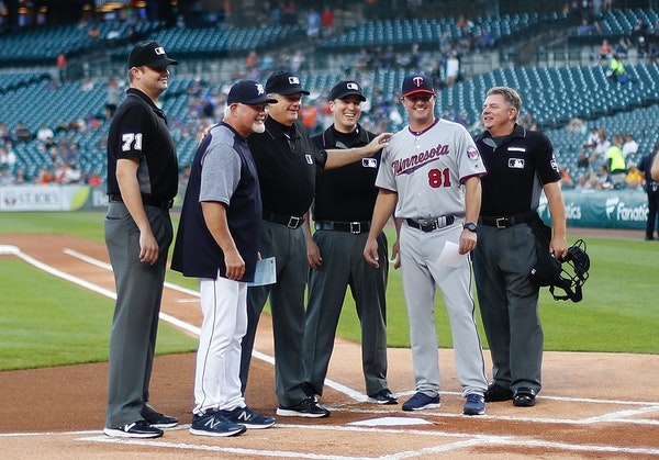 Tigers manager Ron Gardenhire poses with his son, Toby Gardenhire, and umpires, before a baseball game in Detroit on Sept. 17