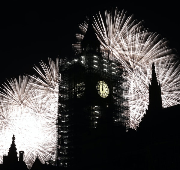 Fireworks explode behind Big Ben, at the Houses of Parliament in London.