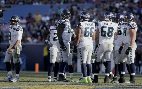 Russell Wilson, left, is having one of his best seasons, thanks to a Seahawks offensive line that has given Wilson time and the Seattle offense balanc