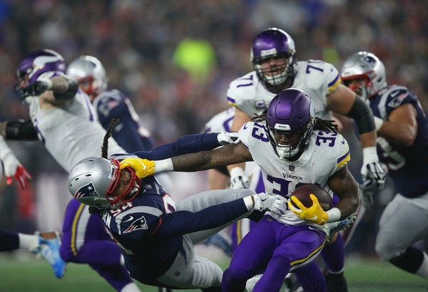 Vikings running back Dalvin Cook (33) fended off Patriots defensive end Adrian Clayborn (94) while ultimately gaining nothing on a fourth-quarter run