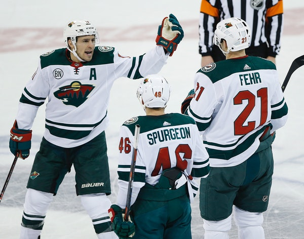 The Wild's Zach Parise (11), Jared Spurgeon (46) and Eric Fehr (21) celebrate a goal against the Winnipeg Jets during the third period Saturday.