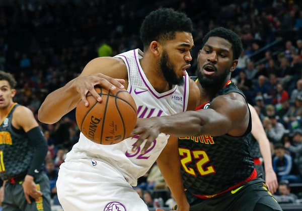 Atlanta's Alex Poythress, right, tries to reach the ball as the Timberwolves' Karl-Anthony Towns drives to the basket in the first half.