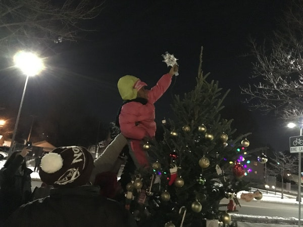 Blessing Caldwell, a first-grader from north Minneapolis, got a boost so she could place a star atop the community Christmas tree outside the Fourth P