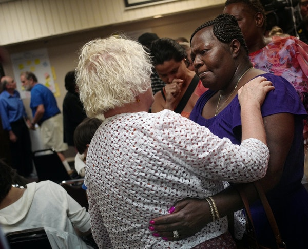 Activist Jacquie Henderson, left, greeted Kimberly Handy Jones, center, the mother of Cordale Handy, who was shot by St. Paul police. She was at Tuesd