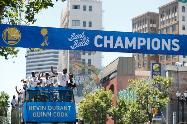 A bus carrying the Golden State Warriors' Kevin Durant and Quinn Cook passed under a champions banner during the team's NBA basketball championship pa
