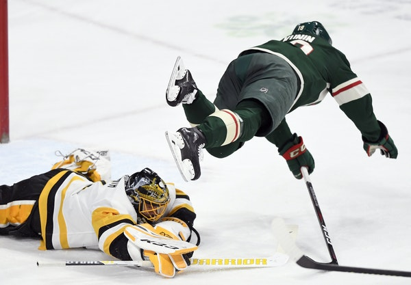 Penguins goalie Casey DeSmith covered up the puck Monday as Wild center Luke Kunin jumped over him during the first period of an eventual 3-2 Pittsbur