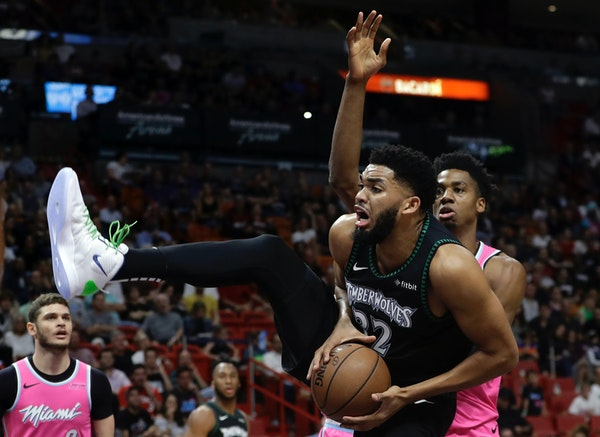 Timberwolves center Karl-Anthony Towns goes to the basket as Heat center Hassan Whiteside defends during the first half