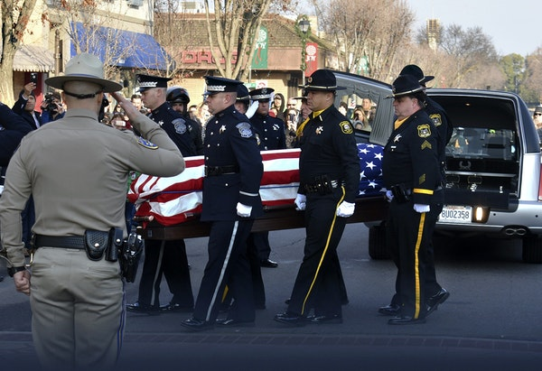 The casket of Police Cpl. Ronil Singh was carried into the Westside Theatre for a public viewing in Newman, Calif., on Friday.