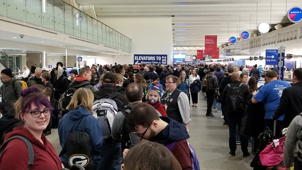 Security lines for the north and south checkpoints at Terminal 1 met in the middle of the terminal Friday, but airport officials blamed holiday travel