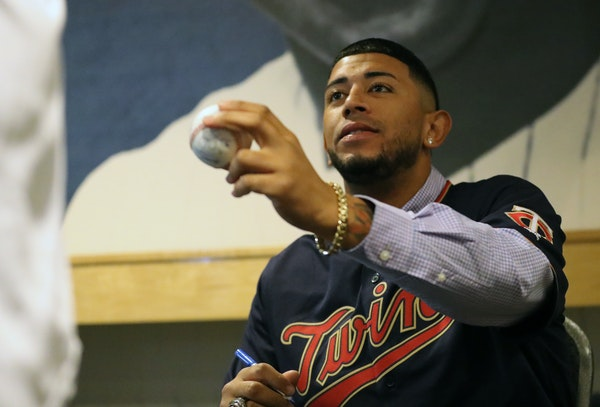 Fernando Romero handed a baseball back to its owner after he autographed it at TwinsFest. He is vying for a starting role, but behind the scenes he is