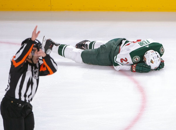 Wild forward Eric Fehr laid on the ice after being checked into the boards by Canadiens left winger Kenny Agostino during the first period Monday.