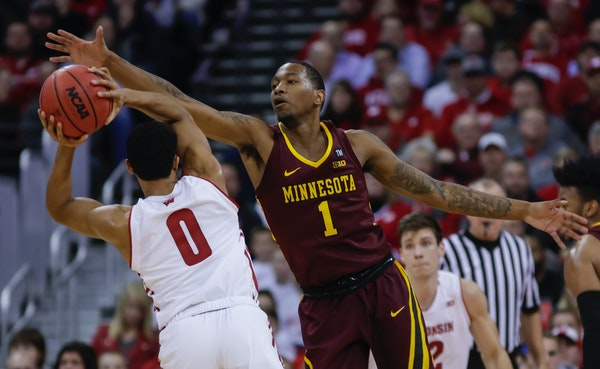 Minnesota's Dupree McBrayer (1) reaches for the ball held by Wisconsin's D'Mitrik Trice (0) during the first half