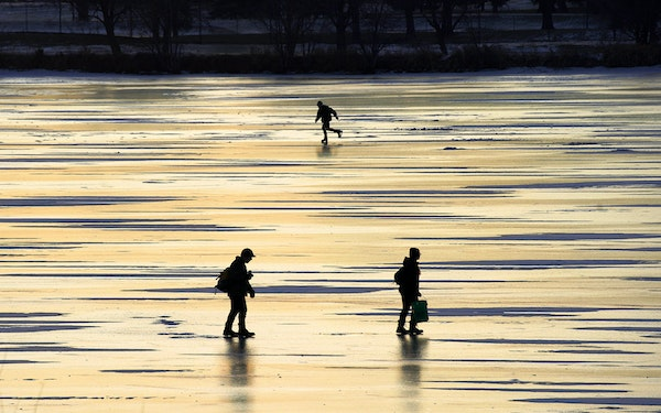On Lake Hiawatha, an ice fishing couple searches for a good spot while a skater glides across the smooth ice.