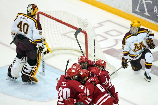 Wisconsin players celebrated with defenseman Peter Tischke (6) after he scored the game winning goal in the third period.