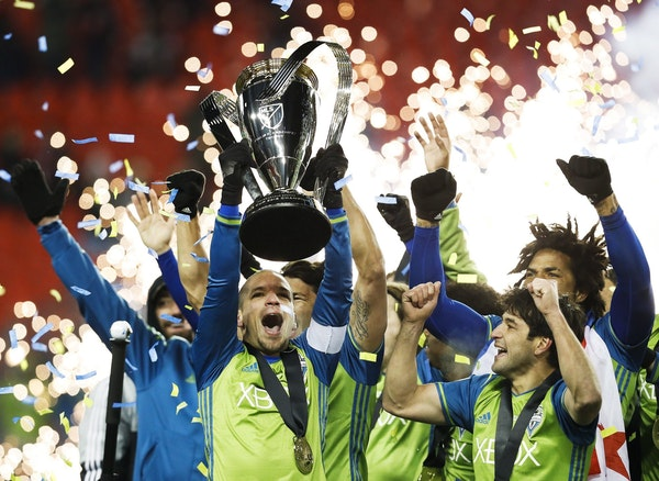 Seattle Sounders midfielder Osvaldo Alonso, front left, hoists soccer's MLS Cup with teammates after defeating Toronto FC on Dec. 10, 2016. Alonso is