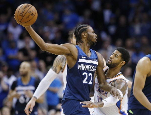 Oklahoma City Thunder forward Paul George, right, defends Minnesota Timberwolves forward Andrew Wiggins (22) in the second half of an NBA basketball g