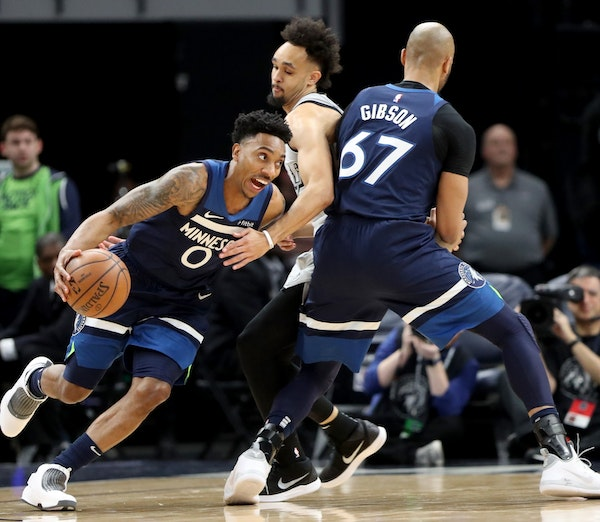 The Minnesota Timberwolves Taj Gibson (67) sets a pick against the San Antonio Spurs' Derrick White (4) for teammate Jeff Teague (0) during the first