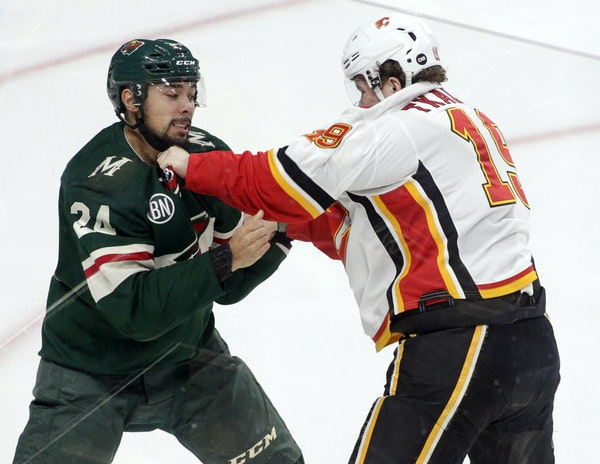 Matt Dumba of the Wild and Matthew Tkachuk of the Flames fought during a game Dec. 15.