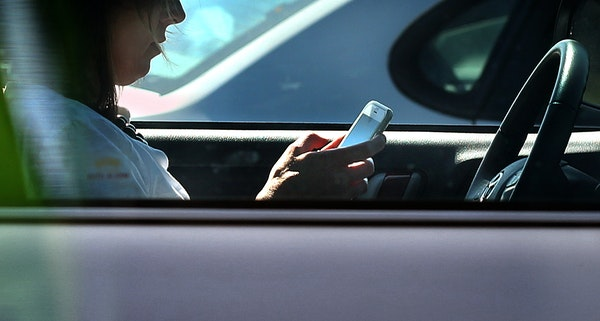 A driver texted on her cellphone while waiting for a traffic light to change in Eagan in 2016. Sixteen states and the District of Columbia now have ha