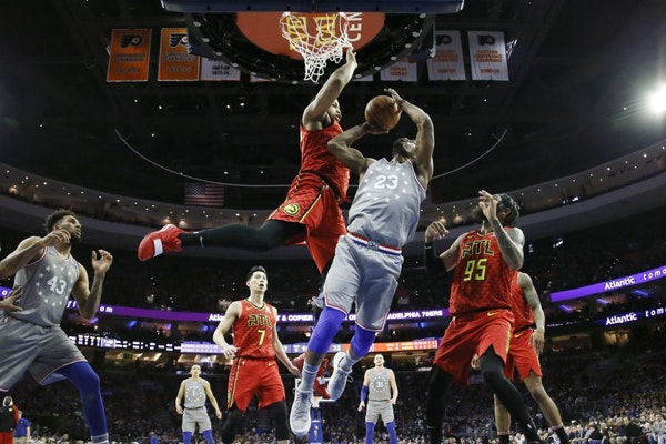 Philadelphia 76ers' Jimmy Butler (23) goes up for a shot between Atlanta Hawks' Omari Spellman (6) and DeAndre' Bembry (95) during the first half of a