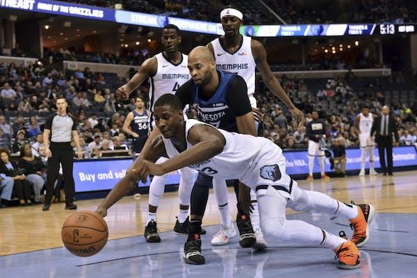Memphis Grizzlies forward Jaren Jackson Jr., (13) dives for a loose ball ahead of Minnesota Timberwolves forward Taj Gibson, center, in the first half