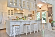 White farmhouse-style kitchen with beadboard ceiling, brick-pattern subway tile and shaker cabinets, the most popular style.