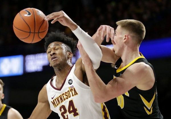 Iowa guard Joe Wieskamp (10) and Minnesota forward Eric Curry (24) vie for the ball during the first half of an NCAA college basketball game Sunday, J