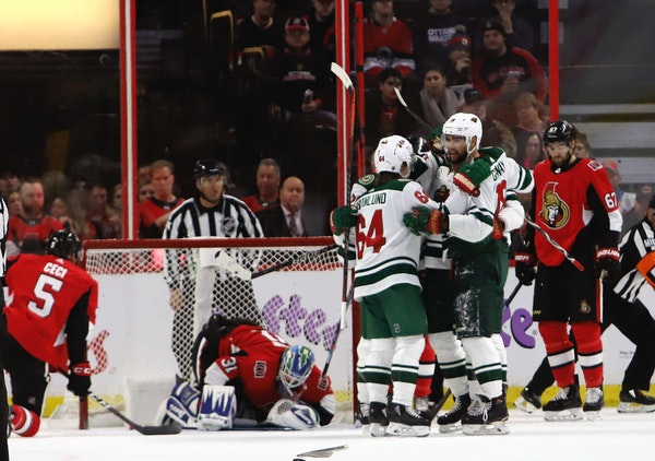 Wild players celebrate a goal against the Senators during the second period Saturday