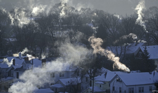 Smoke rises from the chimneys of homes in St. Paul's West 7th neighborhood Wednesday, Jan. 30, 2019, as furnaces tried to keep up with the record brea