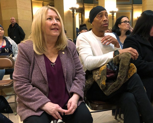 Minnesota state Sen. Chris Eaton, left, and Chazz Smith, right, a cousin of the late rock star Prince, attend a rally at the Minnesota state Capitol i