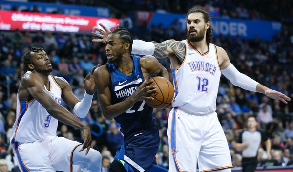 Timberwolves forward Andrew Wiggins drives between Oklahoma City forward Jerami Grant (9) and center Steven Adams (12) in the first half