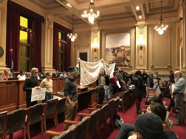Opponents of the Upper Harbor Terminal redevelopment stood with their backs to the Minneapolis City Council following the unanimous approval of the pr