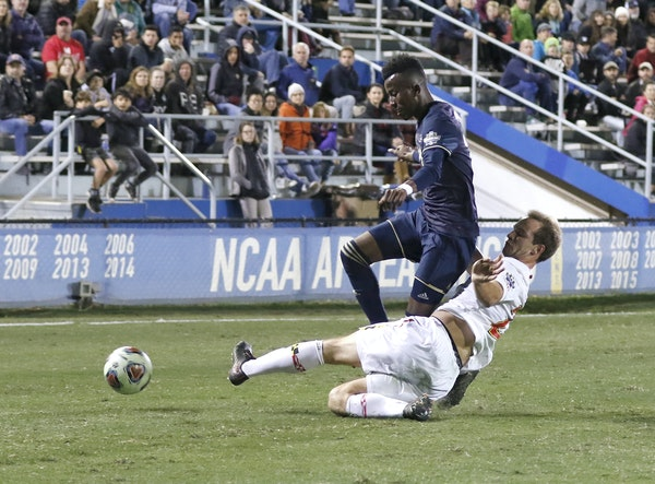 Maryland's Chase Gasper,slide-tackled Akron's Adbi Mohamed, left, during the 2018 NCAA College Cup soccer match Dec. 9. Gasper was selected by Minneso