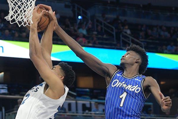 Magic forward Jonathan Isaac blocks a shot by Timberwolves center Karl-Anthony Towns
