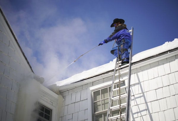 Jake Weber with Ice Dam Guys was steaming off a large ice dam from the gutter of an Edina home on Thursday afternoon.