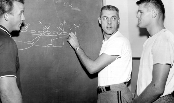 In his first season as Winnipeg coach, 30-year-old Bud Grant drew up a play for quarterback Ken Ploen, right. At left is assistant coach Wayne Robinso