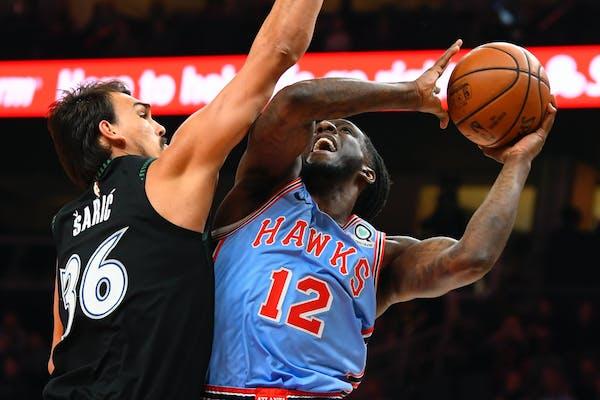 Atlanta forward Taurean Prince shoots as Timberwolves forward Dario Saric defends during the first half