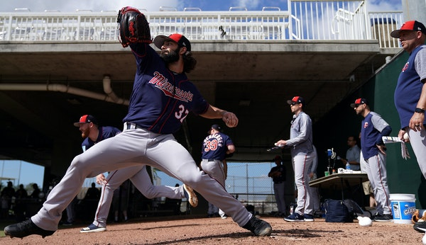 Tim Collins delivered a pitch under the watchful eye of Twins pitching coach Wes Johnson on Feb. 17. Collins, 29, is in camp as a nonroster invitee, t