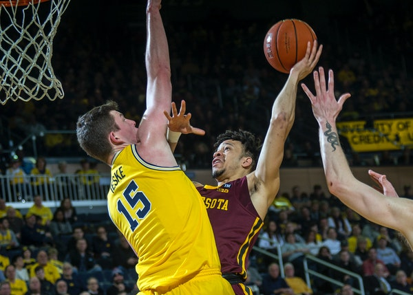 Michigan center Jon Teske defended a shot attempt from Gophers guard Amir Coffey in January.