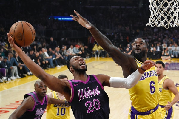 Timberwolves guard Josh Okogie, left, shoots as Los Angeles Lakers guard Lance Stephenson defends during the first half
