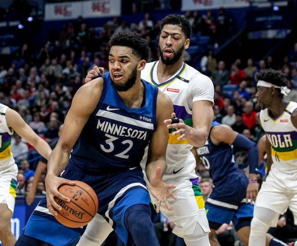 Timberwolves center Karl-Anthony Towns works against New Orleans forward Anthony Davis during the first half