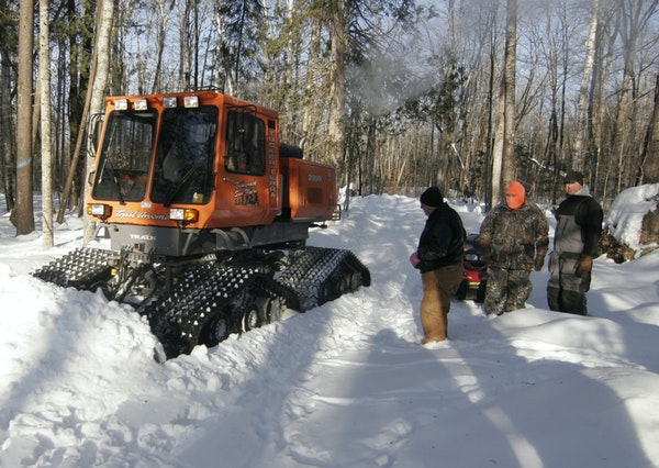 McGregor chapter members of the Minnesota Deer Hunters Association watched a trail being plowed in the woods where emergency deer feeding occurred in