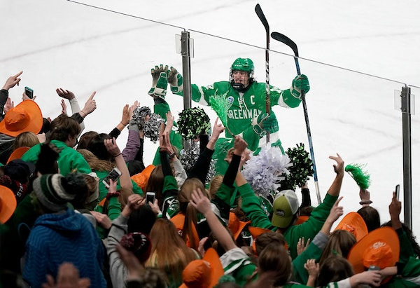 Greenway/Nashwauk-Keewatin forward Donte Lawson (13) celebrates the team's overtime win over Mahtomedi with fans.