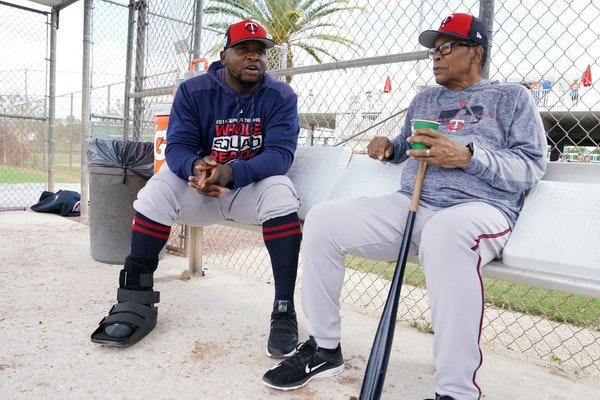 Minnesota Twins third baseman Miguel Sano (22) talked with Twins hall of famer Rod Carew (29) in the dugout at the practice field as he sat out anothe