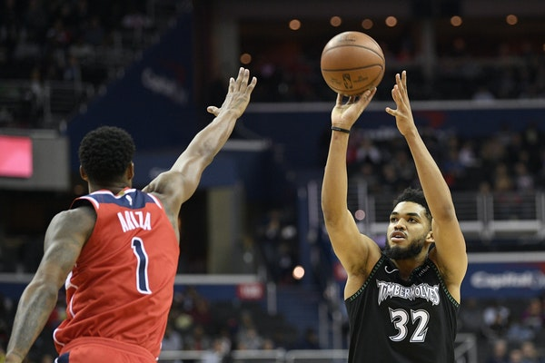 Timberwolves center Karl-Anthony Towns shot over Wizards forward Trevor Ariza during the first half Sunday.