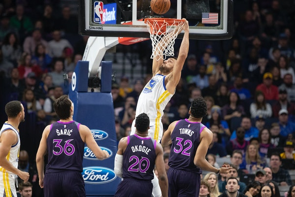 The Warriors' Andrew Bogut dunked over the Timberwolves' defense in Golden State's 117-107 victory at Target Center on Tuesday.