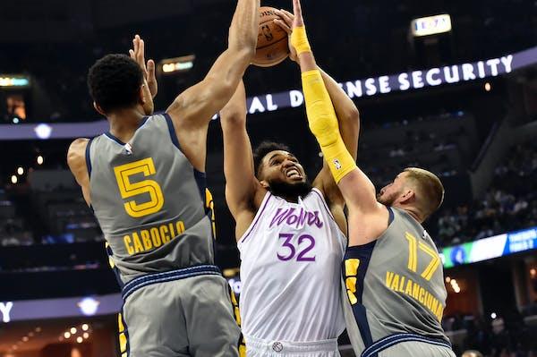 Timberwolves center Karl-Anthony Towns shoots against Memphis center Jonas Valanciunas (17) and forward Bruno Caboclo (5)