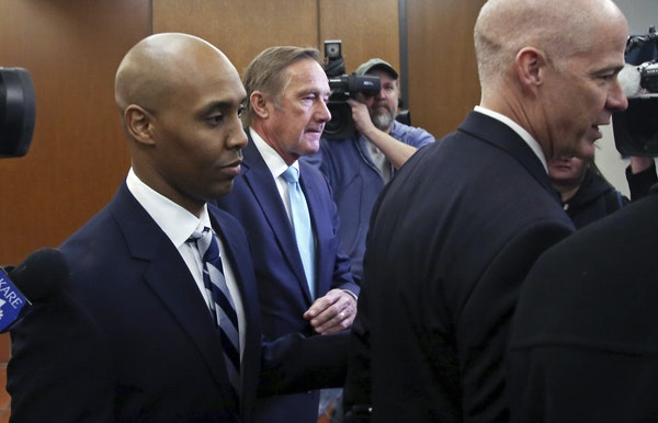 Former Minneapolis police officer, Mohamed Noor, left, leaves the Hennepin County Government Center after a pretrial hearing.