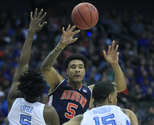 Auburn's Chuma Okeke looked to pass over North Carolina's Nassir Little (5) and Garrison Brooks during the the Tigers' 97-80 victory in a Midwes