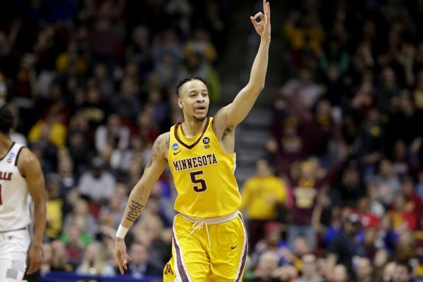 Minnesota's Amir Coffey (5) celebrates a three-point basket during the first half against Louisville. It was one of 11 by the Gophers, who ranked near